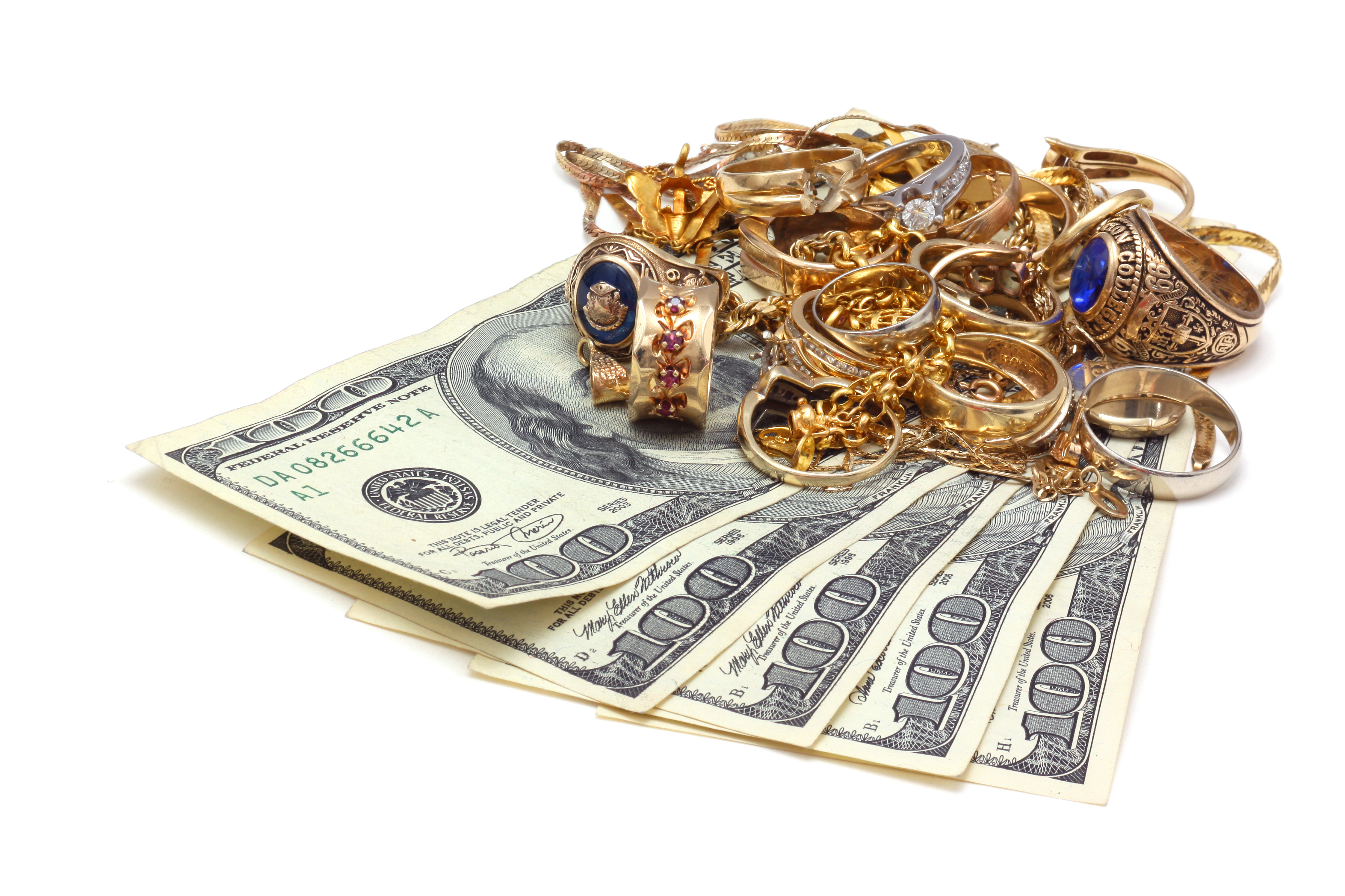 gold jewelry placed on top of five one hundred dollar bills