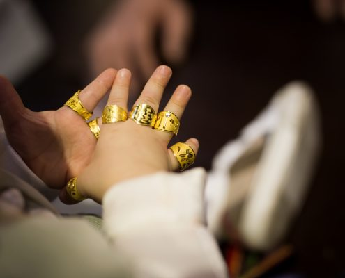Gold rings placed on each finger of person sitting in chair