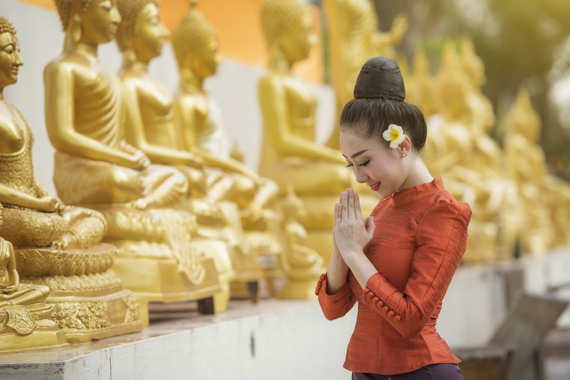 asian woman in front of many gold statues